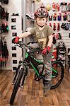 Boy with bicycle helmet in bike shop