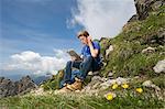 Teenage boy using iPad in mountain landscape