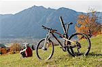 Mountainbiker resting on grass enjoying view