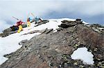 Cross-country skiers climbing mountain rocks