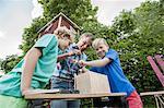Boys father constructing birdhouse garden wood