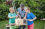 Father boys build birdhouse garden drilling
