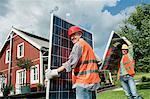 Two workmen installing solar panel house