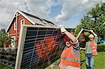 Workmen delivering solar panel house garden