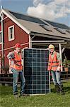 Workmen holding solar panel garden house