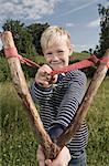 Young boy holding wooden slingshot smiling