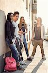 Full length portrait of high school students standing on sidewalk