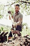 Mature man digging garden with fork