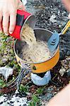 Hand adding noodles into saucepan