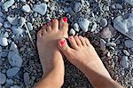 Feet on rocky beach, high angle view