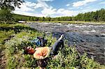 Woman hiker resting at riverbank