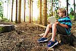 Boy using digital tablet in forest