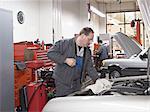 Mechanic checks oil in auto