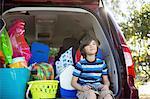 Young boy sitting in hatchback of mini van