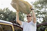 Smiling senior man taking surfboard off car roof rack