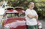 Smiling senior man standing in front of vintage car