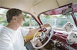 Smiling senior man driving vintage car