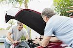 Two senior men talking over car engine