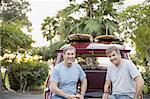 Portrait of smiling senior male friends holding beer bottles on tailgate of vintage car