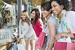 Smiling female friends window shopping