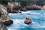 Waves of the Mediterranean Sea crashing on rocky coast at dawn, Cala de Deia, Majorica, Balearic Islands, Spain