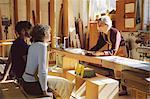 Three craft workers having an informal meeting in pipe organ workshop