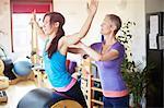 Female student leaning forward onto pilates barrel in pilates gym