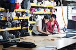 Two seamstresses chalking design onto textile on work table