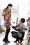 Mature seamstress adjusting length of customers dress in workshop