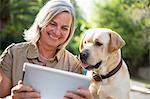 Woman and dog looking at digital tablet