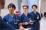 Team of female doctors wearing scrubs talking in hospital ward