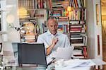 Businessman reading paperwork at home office desk
