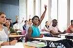 Motivated university students raising their hands at seminar
