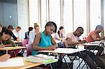 University students taking exam at classroom
