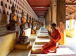 Laos, Vientiane. Young buddhist monk praying, inside famous Wat Sisaket temple (MR)