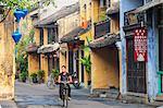Man riding bicycle along street, Hoi An (UNESCO World Heritage Site), Quang Ham, Vietnam