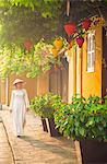 Woman wearing Ao Dai dress walking along street, Hoi An (UNESCO World Heritage Site), Quang Ham, Vietnam (MR)