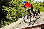 Young female bmx biker speeding down rocks in forest