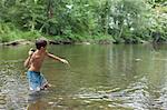 Teenage boy skimming stones in river, Canton, North Carolina, USA