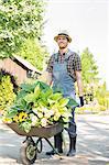 Full-length of gardener pushing wheelbarrow with plants at garden