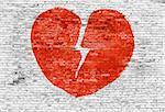 Broken heart painted on white brick wall