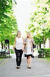 Full length of happy female friends communicating walking on garden path