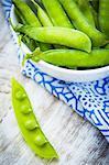 A bowl of fresh mange tout, one pod opened