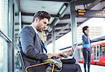 Businessman using laptop at train station