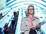 Businesswoman carrying folders near escalator