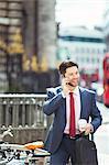 Businessman talking on cell phone on city sidewalk