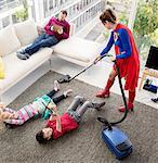 Superhero vacuuming around family in living room