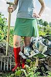 Woman vegetable garden fork wellington boots