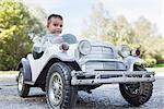 Small boy sitting driving model vintage car