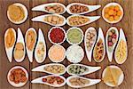 Crisp and dip party snack food selection in porcelain bowls over oak background.